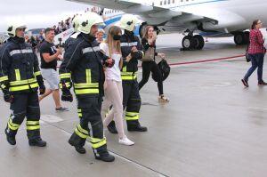 Zawiązane oczy, eskorta strażaków. Niespodzianka na płycie lotniska